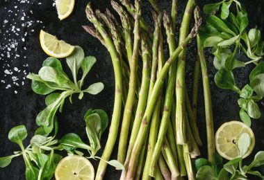 Bundle of young raw uncooked organic green asparagus with green salad leaves, sliced lemon and sea salt over black texture background. Top view. Healthy eating