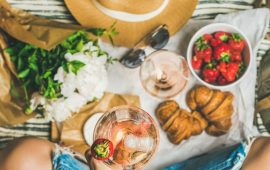 French style romantic picnic setting. Woman in jeans with glass of rose wine, fresh strawberries, croissants, brie cheese, sunglasses, peony flowers on blanket, top view. Outdoor gathering concept