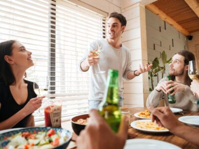 Group of happy young people drinking and celebrating at the table at home